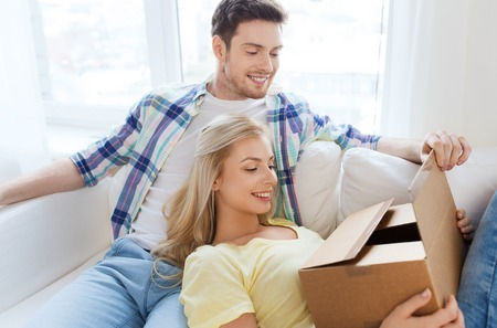 parcel: people, delivery, mail, shipping and moving concept - smiling couple with cardboard box at home Stock Photo
