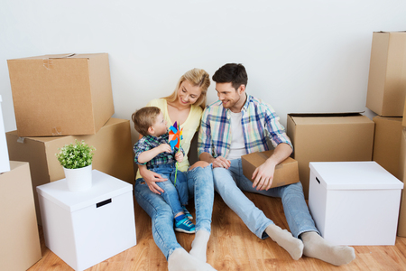 mortgage, people, housing and real estate concept - happy family with boxes moving to new home