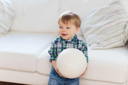kiddy: childhood and people concept - happy little baby boy with ball at home
