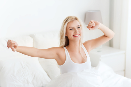 rest, sleeping, comfort and people concept - happy young woman stretching in bed after waking up at home bedroom