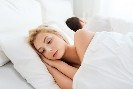 lying on back: people, health, sleep disorder concept - couple lying back to back in bed at home and young woman suffering from insomnia