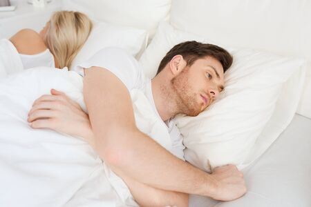 lying on back: people, health, sleep disorder concept - couple lying back to back in bed at home and young man suffering from insomnia
