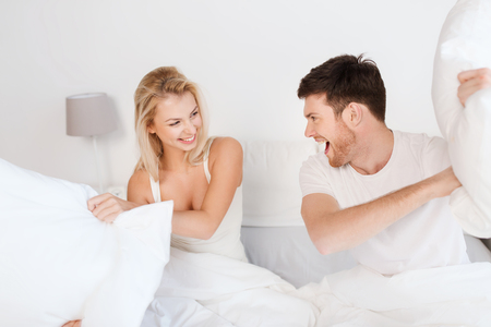 couple fight: people, family, fun, bedtime and fun concept - happy couple having pillow fight in bed at home