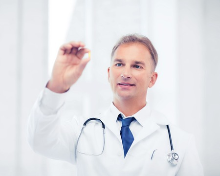 doctor fish wellness fish: healthcare and medical concept - doctor holding omega 3 capsule Stock Photo