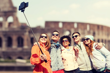 europe travel: tourism, travel, people, leisure and technology concept - group of smiling teenage friends taking selfie with smartphone and monopod over coliseum ruins in rome background