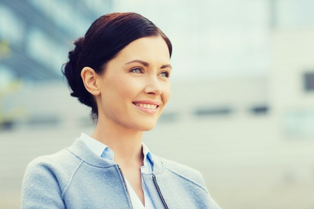 aside: business and people concept - young smiling businesswoman over office building Stock Photo