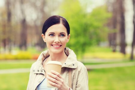 take away: drinks, leisure and people concept - smiling woman drinking coffee in park