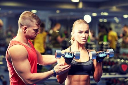 fitness, sport, musculation et haltérophilie concept - jeune femme et un entraîneur personnel avec des haltères fléchissant les muscles dans une salle de sport