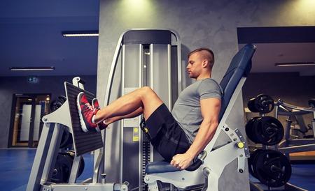 sport, fitness, kulturystyka, styl życia, a ludzie koncepcji - człowiek sprawowanie i wyginanie mięśni nóg na maszynie siłowni