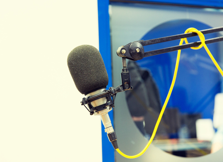 transmitting device: technology, electronics and audio equipment concept - close up of microphone at recording studio or radio station