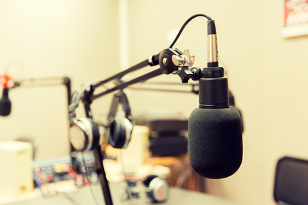 fm: technology, electronics and audio equipment concept - close up of microphone at recording studio or radio station
