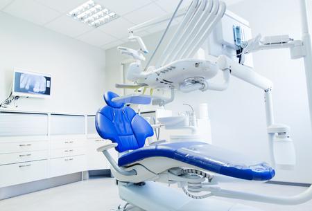 odontología, medicina, equipos médicos y el concepto de la estomatología - interior de la nueva oficina de la clínica dental moderna con la silla Foto de archivo