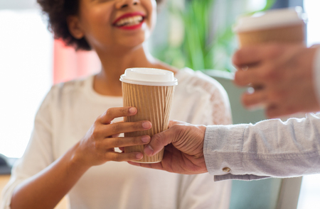 people, drinks and care concept - close up of happy african american woman hand taking coffee cup from man