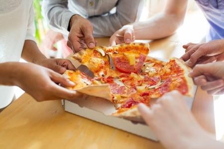 personas comiendo: alimentos, el almuerzo y la gente concepto - cerca de amigos o gente que come la pizza