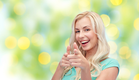 summer holidays: gesture, summer and people concept - happy smiling young woman or teenage girl pointing finger to you over green lights background