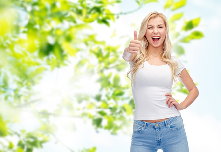 emotions, expressions, advertisement, summer and people concept - happy smiling young woman or teenage girl in white t-shirt showing thumbs up over green natural background