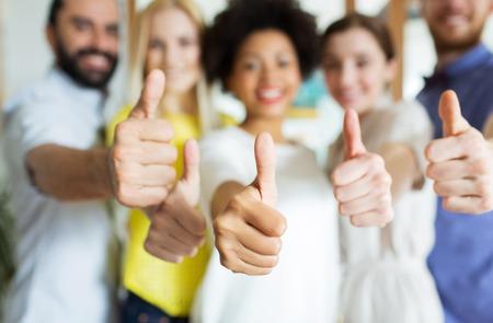 бизнес, вводу в эксплуатацию, люди, жест и концепция коллективной работы - крупным планом счастливой улыбкой творческая команда показывает палец вверх в офисе
