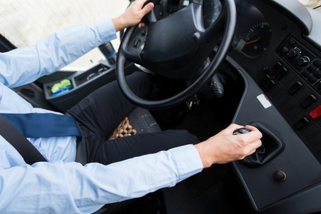 transport, transportation, tourism, road trip and people concept - close up of bus driver steering wheel and driving passenger bus 스톡 콘텐츠