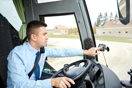 public address: transport, transportation, navigation and people concept - bus driver entering address to gps navigator