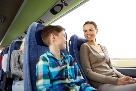 madre e hijo: travel, tourism, family, technology and people concept - happy mother and son riding in travel bus Foto de archivo