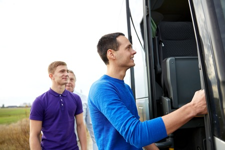 go inside: transport, tourism, road trip and people concept - group of happy male passengers boarding travel bus