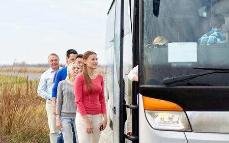 транспорт: транспорт, туризм, путешествие на автомобиле, и люди концепция - Группа счастливых пассажиров, садящихся автобусных путешествий