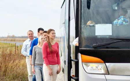 transport: vervoer, toerisme, road trip en mensen concept - groep gelukkige passagiers die bus reizen Stockfoto
