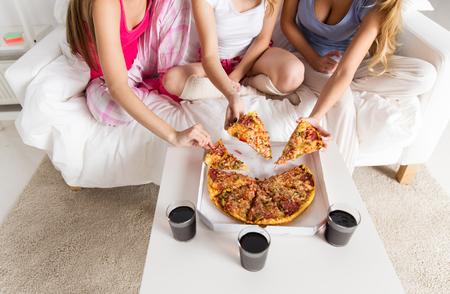 amistad, gente, fiesta de pijamas y la comida chatarra concepto - cerca de amigos o adolescentes comiendo pizza en casa Foto de archivo
