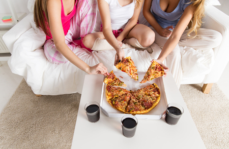 pajama: friendship, people, pajama party and junk food concept - close up of friends or teenage girls eating pizza at home