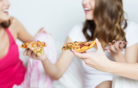 friendship, people, pajama party and junk food concept - close up of happy friends or teenage girls eating pizza at home