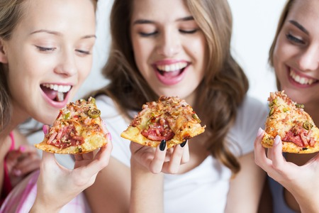 pajama: friendship, people, pajama party and junk food concept - close up of happy friends or teenage girls eating pizza at home