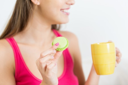 pj's: friendship, people, pajama party and junk food concept - close up of happy woman or teen girl with tea cup eating macaroon cookie at home Stock Photo