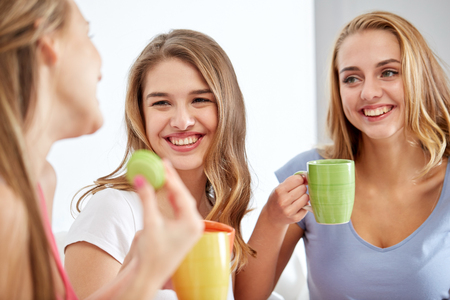 pj's: friendship, people, pajama party and communication concept - happy friends or teenage girls drinking, chatting tea and eating sweets at home