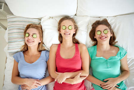 face mask: people, beauty, natural cosmetics and pajama party concept - happy friends or teenage girls with cucumber mask having fun and lying in bed at home Stock Photo