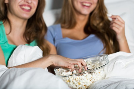 pj's: friendship, people, pajama party, entertainment and junk food concept - close up of happy friends or teenage girls eating popcorn and watching movie or tv series at home