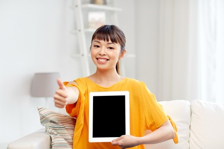 people, technology, gesture, advertisement and leisure concept - happy young asian woman sitting on sofa and showing tablet pc computer blank black screen and thumbs up at home