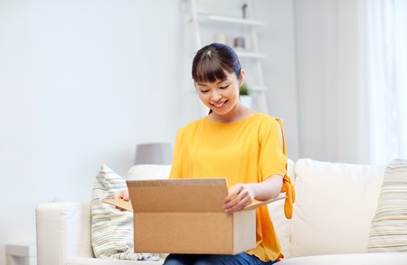 delivery box: people, delivery, commerce, shipping and shopping concept - happy asian young woman with cardboard parcel box at home Stock Photo