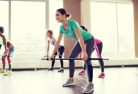 fitness gym: fitness, sport, training, gym and lifestyle concept - group of people exercising with bars in gym