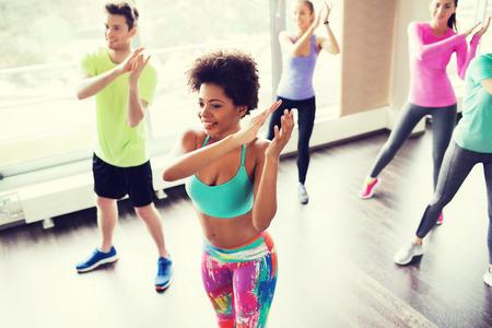 fitness, deporte, la danza y el concepto de estilo de vida - grupo de gente sonriente con el entrenador bailando en el gimnasio o estudio