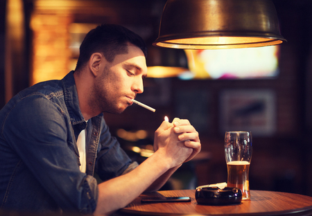 addiction drinking: people, smoking and bad habits concept - man drinking beer and lighting cigarette at bar or pub