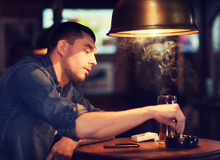 malos habitos: people, lifestyle and bad habits concept - man drinking beer and smoking and extinguishing his cigarette at bar or pub