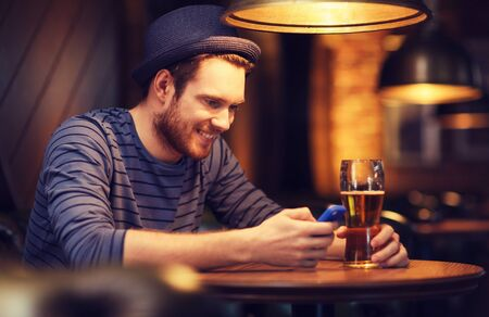 people and technology concept - happy man with smartphone drinking beer and reading message at bar or pub Stock Photo