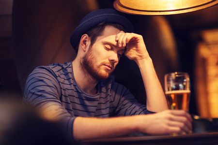 alcoholic man: people, loneliness, alcohol and lifestyle concept - unhappy single young man in hat drinking beer at bar or pub