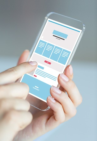 web screen: business, technology and people concept - close up of woman hand holding and showing transparent smartphone web page design on screen