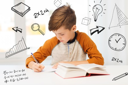 book concept: education, childhood, people, homework and school concept - student boy with book writing to notebook at home over mathematical doodles