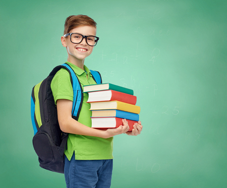 childhood, education and people concept - happy smiling student boy in eyeglasses with school bag and books over green school chalk board background Banco de Imagens