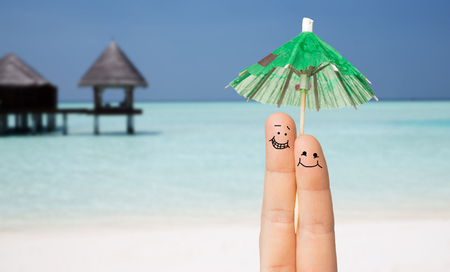 cocktail umbrella: gesture, love, holidays, summer vacation and body parts concept - close up of two fingers with cocktail umbrella decoration Stock Photo
