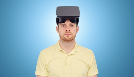entertainment concept: 3d technology, virtual reality, entertainment and people concept - young man with virtual reality headset or 3d glasses over blue background Stock Photo