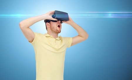entertainment background: 3d technology, virtual reality, entertainment and people concept - happy young man with virtual reality headset or 3d glasses playing game over blue background and laser light
