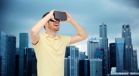 mediated: 3d technology, virtual reality, entertainment and people concept - happy young man with virtual reality headset or 3d glasses over singapore city skyscrapers background Stock Photo